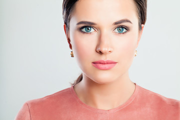 Young beautiful woman face, closeup portrait. Female model with perfect makeup on background with copy space