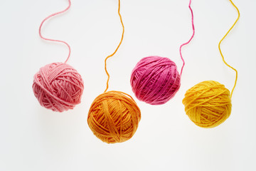 Collection of colorful woolen balls, partially unrolled.