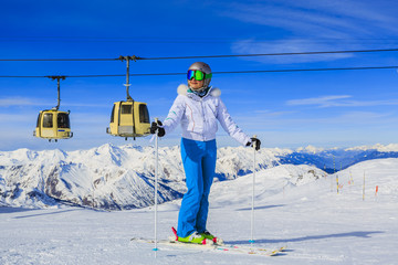 Fototapete - Girl on skiing on snow on a sunny day in the mountains. Ski in winter seasonon, the tops of snowy mountains in sunny day. Meribel resort, 3 vallees, France.