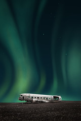 green northern lights over the wreck of a white airplane
