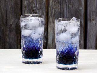 Two crystal glasses filled with layered butterfly pea flowers (Clitoria ternatea) soda, with homemade blue pea flowers syrup, ice cubes and carbonated water