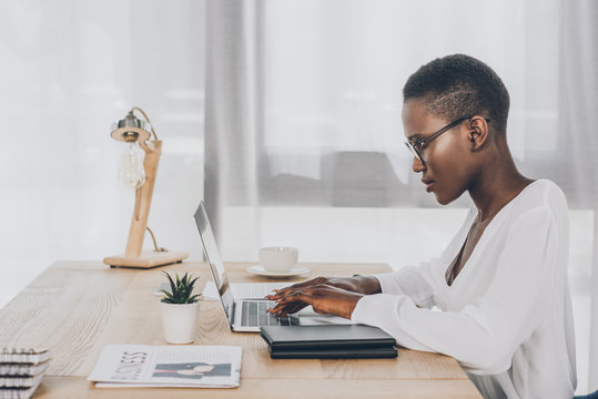 side view of stylish attractive african american businesswoman working at laptop in office