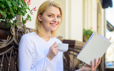 Find opportunity to read more. Girl drink coffee while read bestseller book by popular author. Mug coffee and interesting book best combination perfect weekend. Woman have drink cafe terrace outdoors