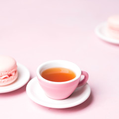 Still life with french delicious dessert macaroons and cup of coffee on pink background with copy space