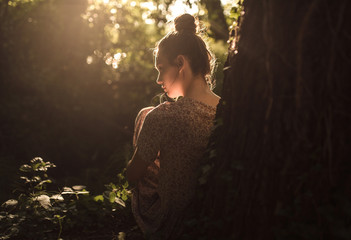 Young brunette with a hair bun sitting and relaxing under a tree sunlight through tree leaves