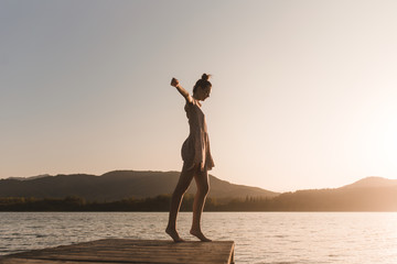 Side view of young caucasian girl dancing on the edge of a dock of a lake in a sunset of a day of summer mountains background