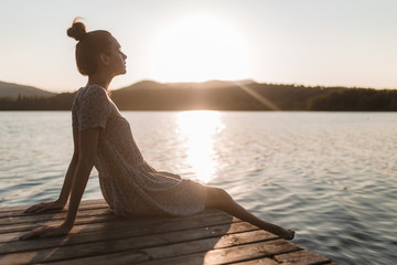 Young caucasian girl sitting and relaxing on a dock of a lake in a sunset of summer mountains background