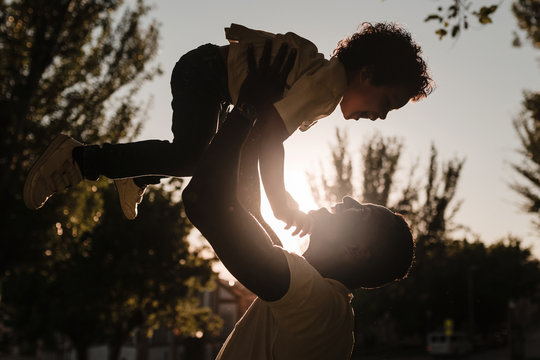 African father raises his son with his arms sunset background
