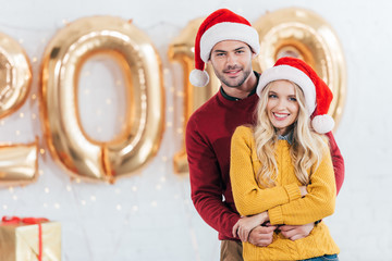 8fd82a6440160 beautiful smiling couple in santa hats hugging at home with 2019 new year  golden balloons