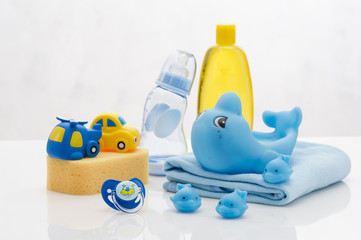 Still life with babt hygiene and bath items, shampoo bottle, essential oil, baby soap, towel, pacifier, rubber toy, shower puff