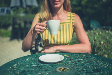 Woman drinking coffee in garden of cafe