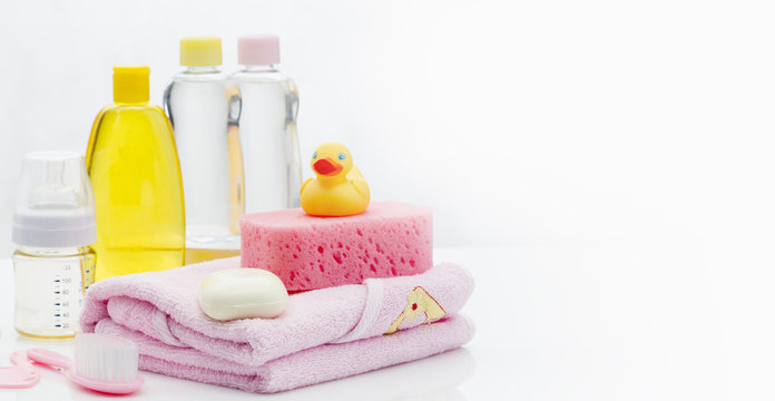 Still life with baby hygiene and bath items, shampoo bottle, essential oil, baby soap, towel, pacifier, rubber toy, shower puff. Copy space for your text