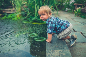 Little toddler playing near a pond