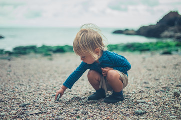 Toddler playing with stones on the beach
