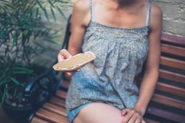 Woman on bench with nut butter on bread