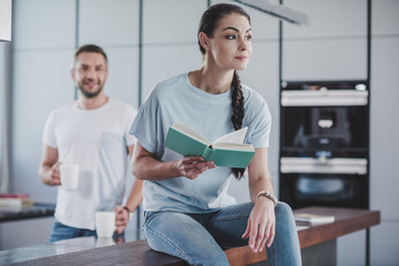 attractive girlfriend sitting on kitchen counter with open book and looking away
