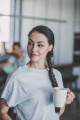 close up portrait of attractive smiling woman with coffee cup at home