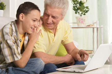 Grandfather with grandson using laptop at home