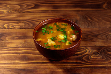 Kharcho soup with meat and rice on wooden table