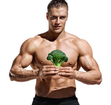 Sporty man holding broccoli as symbol healthy food. Photo of handsome man with naked torso and good physique on white background. Healthy lifestyle