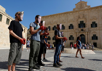 Protesters from humanitarian rescue NGOs Lifeline and Sea-Watch wear masks depicting European Union leaders and handcuffs on bloodstained hands during a protest outside the Auberge de Castille, the office of Maltese PM Muscat, in Valletta