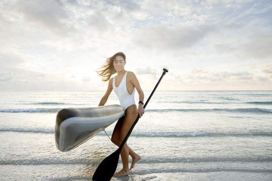 Miami woman at the beach carrying a paddle board at sunrise