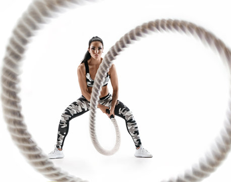 Woman doing exercises with battle rope. Photo of muscular model in military sportswear isolated on white background. Strength and motivation