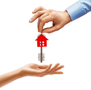 Man's hand giving the house key to woman's hand isolated on white background. Close up. High resolution product