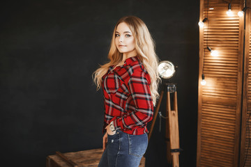 Beautiful and fashionable blonde pluss-size model girl with big breast in red plaid shirt and in a jeans, stands near the wooden chest and posing in studio at dark interior