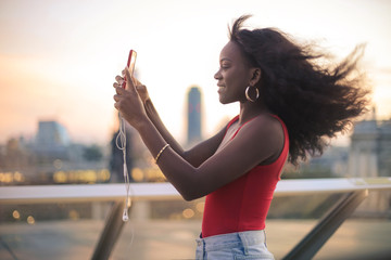 Girl making photos with her phone from a rooftop