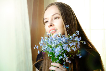 Close-up of a sensual portrait of an attractive girl with forget-me-nots