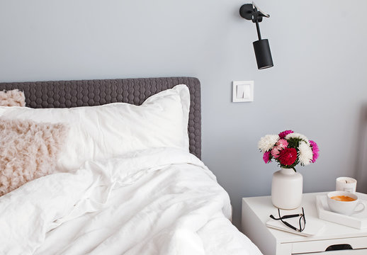 Part of bedroom in the morning with flowers and coffee on the nightstand