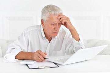 Portrait of confident senior businessman with laptop