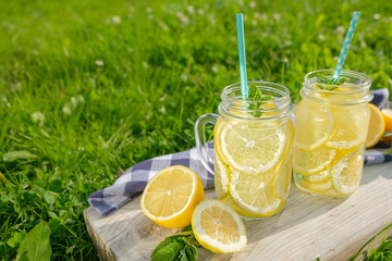 Lemonade in jars of hipster for jam on a background of green grass. Concept: picnic with refreshing drinks