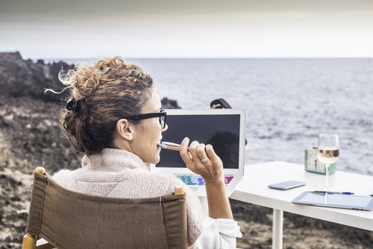freedom and lifestyle for young woman at work in front of the ocean with no rooms and offices. laptop open and lady thinking at his career and his life. enjoying freedom and alternative work concept