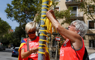 Women place yellow ribbons during Catalonia's national day 'La Diada' in Barcelona