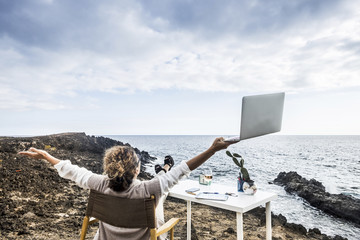 Middle age woman working in aleternative office in freedom in front of the ocean with no walls and buildings around. success and happiness concept for people at work. business and technology laptop