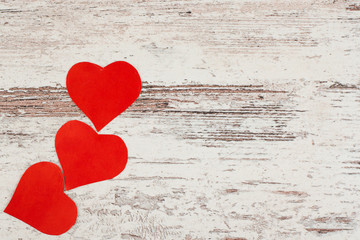 3  red Love hearts on white-painted wooden texture background wi