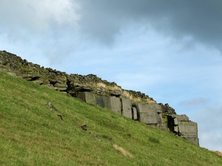 A dramatic stone outcrop on a steep green hillside in yorkshire moors landscape with the remains of an old dry stone wall along the top against a cloudy blue sky