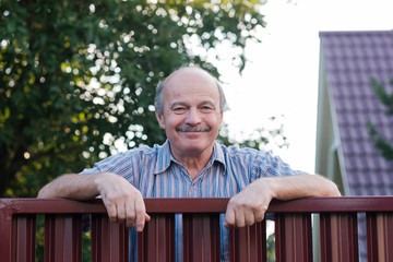Portrait of a happy handsome mature man standing leaning on the red metal fence