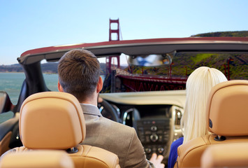 road trip, travel and people concept - close up of couple driving in convertible car from back over golden gate bridge in san francisco bay background
