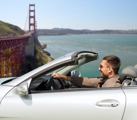 road trip, travel and people concept - happy man driving convertible car over golden gate bridge in san francisco bay background