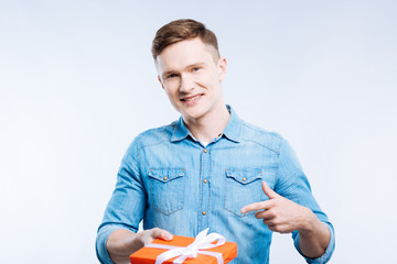 Your gift. Cheerful handsome man smiling while pointing at the gift box