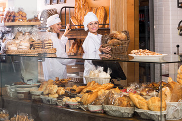 Smiling women selling fresh pastry and loaves