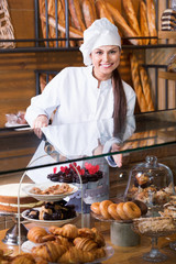 Portrait of friendly  young woman at bakery display