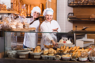 Bakery staff offering bread and different pastry for sale