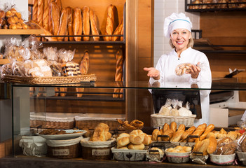 Mature woman selling fresh pastry and baguettes