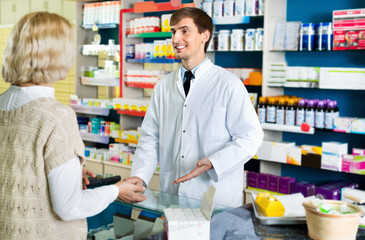 Friendly smiling pharmacist counseling female customer