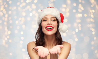036975425a0fe christmas and holidays concept - happy smiling young woman with empty hands  in santa hat over
