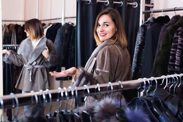 Woman trying on sheepskin coat in women's cloths store